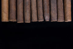 Rolled cigars in a group on black stock photography