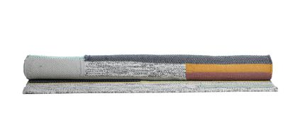 Rolled colorful carpet on white background. Interior element stock photos