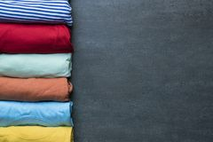 Rolled colorful clothes on black background. Close up of rolled colorful clothes on black background Royalty Free Stock Photos