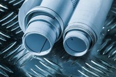 Rolled construction drawings on channeled metal sheet.  royalty free stock photos