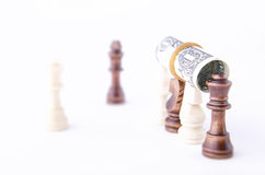 Rolled Dollar Bill on Top of Chess Pieces Royalty Free Stock Photo