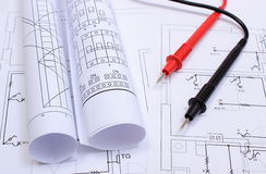 Rolled electrical diagrams and cables of multimeter on drawing of house Royalty Free Stock Image
