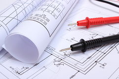 Rolled electrical diagrams and cables of multimeter on drawing of house Stock Image