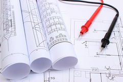Rolled electrical diagrams and cables of multimeter on drawing of house. Rolls of electrical diagrams and cables of multimeter lying on construction drawing of Royalty Free Stock Image