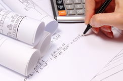Rolled electrical diagrams, calculator and mathematical calculations Royalty Free Stock Photo