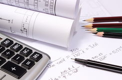 Rolled electrical diagrams, calculator and mathematical calculations Royalty Free Stock Image