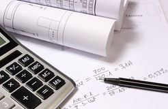 Rolled electrical diagrams, calculator and mathematical calculations Stock Photography