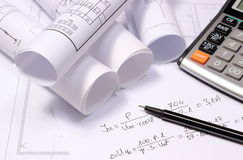 Rolled electrical diagrams, calculator and mathematical calculations Royalty Free Stock Images