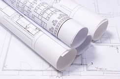 Rolled electrical diagrams on construction drawing of house Royalty Free Stock Photo