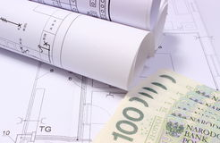 Rolled electrical diagrams on construction drawing of house and money Stock Photos