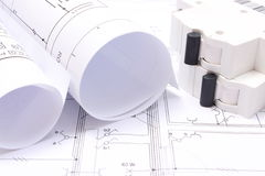 Rolled electrical diagrams and electric fuse on construction drawing of house Royalty Free Stock Photography
