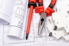 Rolled electrical diagrams, electric fuse and work tools on construction drawing of house. Rolled electrical diagrams, electric fuse and work tools lying on stock photos