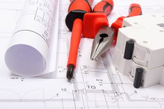 Rolled electrical diagrams, electric fuse and work tools on construction drawing of house. Rolled electrical diagrams, electric fuse and work tools lying on stock photo