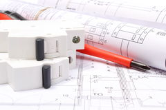 Rolled electrical diagrams, electric fuse and work tools on construction drawing of house Royalty Free Stock Photo