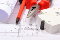 Rolled electrical diagrams, electric fuse and work tools on construction drawing of house Royalty Free Stock Image