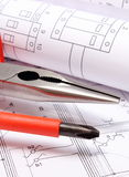 Rolled electrical diagrams and work tools on construction drawing of house Stock Photography