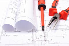 Rolled electrical diagrams and work tools on construction drawing of house Royalty Free Stock Photography