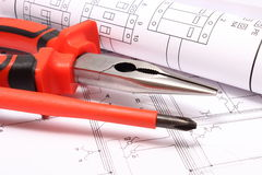 Rolled electrical diagrams and work tools on construction drawing of house Stock Photos