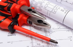 Rolled electrical diagrams and work tools on drawing. Rolls of electrical diagrams with work tools lying on construction drawing of house, drawings for the stock photos