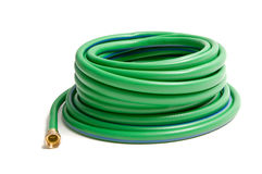 Rolled garden hose. A rolled up garden hose isolated on white royalty free stock images