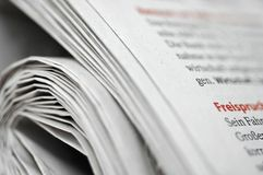 Rolled German newspaper. German newspaper rolled up but showing parts of article Royalty Free Stock Photo