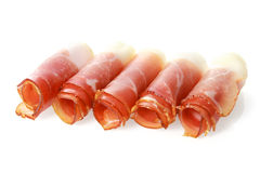Rolled gourmet proscuitto or parma ham. Presentation of gourmet proscuitto or parma ham in thin dry-cured slices rolled and arranged in a row over white Royalty Free Stock Photo