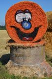 Rolled hay bale decorated with pumpkin face. This is a rolled hay bale painted orange with a pumpkin face for Halloween on a farm in Gervis, Oregon stock image
