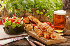 Rolled hot dog sausages baked in puff pastry with salad and beer Royalty Free Stock Photography