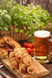 Rolled hot dog sausages baked in puff pastry with salad and beer Stock Photos