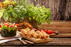 Rolled hot dog sausages baked in puff pastry with salad and spac Stock Image