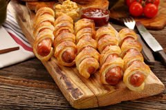 Rolled hot dog sausages baked in puff pastry royalty free stock photography