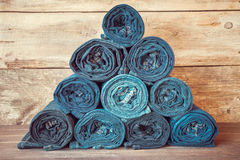 Rolled jeans stack on wooden background. Royalty Free Stock Image