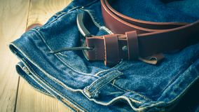 Rolled leather belt and old blue jean. Rolled leather belt place on old blue jean, vintage color effect stock images