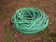 Rolled long garden hose. Rolled long garden hose on ground stock images