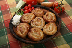 Rolled  meat pies. On clay plate with cheese Royalty Free Stock Photography