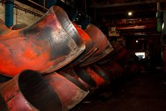 Rolled metal pipes of large diameter are in the production workshop.  royalty free stock images