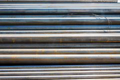 Rolled metal pipes stacked. Parallel to each other royalty free stock photography
