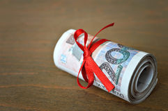 Rolled money tied with red ribbon Royalty Free Stock Image