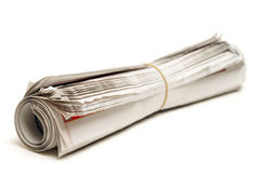 Rolled Newspaper. An isolated newspaper that has been rolled and banded Stock Photo