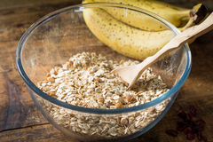 Rolled oats, bananas, nuts and spices in bowl on wooden table Royalty Free Stock Images
