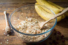 Rolled oats, bananas, nuts and spices in bowl on wooden table Royalty Free Stock Image