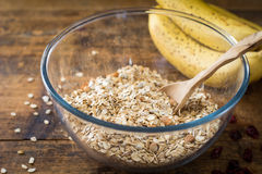 Rolled oats, bananas, nuts and spices in bowl on wooden table Stock Photography