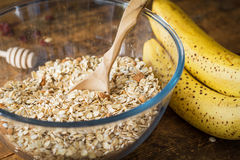 Rolled oats, bananas, nuts and spices in bowl on wooden table Royalty Free Stock Photography