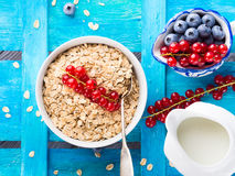 Rolled Oats and berries on blue textured background. Bowl with rolled oats oatmeal flakes with red currants for healthy breakfast on bright blue wooden Royalty Free Stock Photo