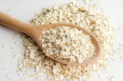 Rolled oats in big spoon. Rolled oats in big wooden spoon, healthy food concept royalty free stock images