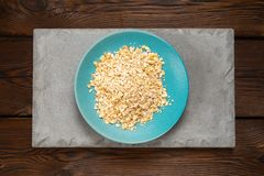 Rolled oats in a blue bowl on a concrete tile on a dark background stock image