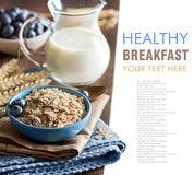 Rolled oats in a bowl with berries and milk Stock Photography