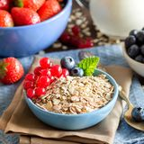 Rolled oats in a bowl with berries and milk Royalty Free Stock Image