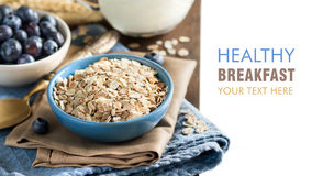 Rolled oats in a bowl with blueberries and milk Royalty Free Stock Photos