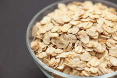 Rolled oats in a glass bowl. On black background. Close-up Stock Image
